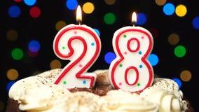 Nr. 28 auf Kuchen - achtundzwanzig Geburtstagskerze Burning - brennen Sie heraus am Ende durch Farbe unscharfer Hintergrund stock video