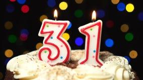 Nr. 31 auf Kuchen - dreißig ein Geburtstagskerze Burning - brennen Sie heraus am Ende durch Farbe unscharfer Hintergrund stock video