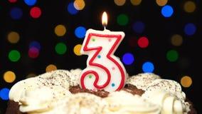 Nr. 3 auf Kuchen - eine drei-Geburtstags-Kerze Burning - brennen Sie heraus am Ende durch Farbe unscharfer Hintergrund stock footage