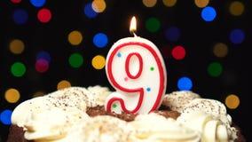 Nr. 9 auf Kuchen - eine neun-Geburtstags-Kerze Burning - brennen Sie heraus am Ende durch Farbe unscharfer Hintergrund stock footage
