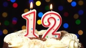 Nr. 12 auf Kuchen - eine zwölf-Geburtstags-Kerze Burning - brennen Sie heraus am Ende durch Farbe unscharfer Hintergrund stock footage