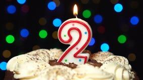 Nr. 2 auf Kuchen - eine zwei-Geburtstags-Kerze Burning - brennen Sie heraus am Ende durch Farbe unscharfer Hintergrund stock video