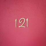 Nr. 121 auf roter Wandbeschaffenheit Stockbild