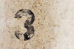 Nr. drei 3 auf Betonmauerhintergrund Stockbild