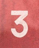 Nr. drei, weiße Bahnzahl auf Gummirennbahn Stockfotos