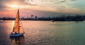 När du seglar yachten skriver in den Varna hamnen på solnedgången Arkivbilder