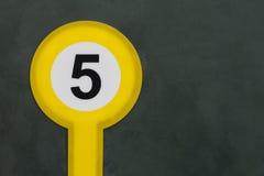 Nr. fünf auf der Steinwand grün gemalt im runden gelben Zeichen Lizenzfreies Stockfoto