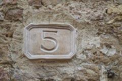 Nr. fünf auf einer Wand Stockbild