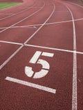 Nr. fünf Große weiße Bahnzahl auf Laufgummirennbahn Lizenzfreie Stockbilder