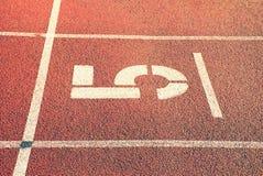 Nr. fünf Große weiße Bahnzahl auf roter Gummirennbahn Leichte strukturierte laufende Rennbahnen im athletischen Stadion Stockfotos