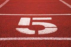 Nr. fünf Große weiße Bahnzahl auf roter Gummirennbahn Leichte strukturierte laufende Rennbahnen im Stadion Stockfotos