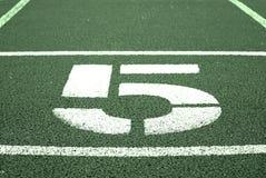 Nr. fünf Große weiße Bahnzahl auf roter Gummirennbahn Leichte strukturierte laufende Rennbahnen im Stadion Lizenzfreies Stockbild