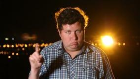 Nr, jonge mens die aanbieding verwerpen door vinger bij nacht, portret te golven stock video