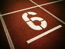 Nr. sechs Weiße athletische Bahnzahl auf roter Gummirennbahn Stockfoto