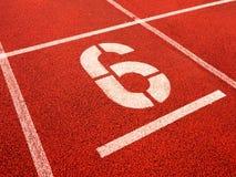 Nr. sechs Weiße athletische Bahnzahl auf roter Gummirennbahn Stockfotos