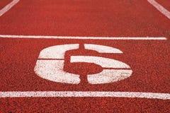 Nr. sechs Weiße athletische Bahnzahl auf roter Gummirennbahn, Beschaffenheit von Rennbahnen im Stadion Stockfotos