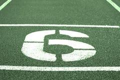 Nr. sechs Weiße athletische Bahnzahl auf roter Gummirennbahn, Beschaffenheit von Rennbahnen im Stadion Stockbilder