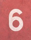Nr. sechs, weiße Bahnzahl auf Gummirennbahn Stockfotos