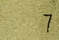 Nr. sieben auf gelber Schmutzwandoberfläche Stockfotos