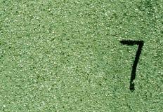 Nr. sieben auf grüner gruhge Wandoberfläche Stockfotos