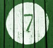Nr. sieben auf grüner hölzerner Wand Stockfoto