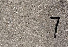 Nr. sieben auf grauer gruhge Wandoberfläche Stockfotografie