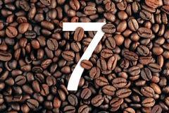 Nr. sieben auf Kaffeebohne-Hintergrundkonzept Stockfotografie