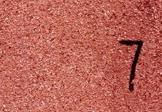 Nr. sieben auf roter Schmutzwandoberfläche Lizenzfreies Stockbild