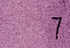 Nr. sieben auf violetter Schmutzwandoberfläche Lizenzfreie Stockfotos