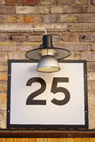 Nr 25 sign on building with porch light. Number twenty-five street number on brick wall Stock Photo