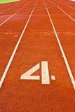 Nr. vier auf dem Anfang einer laufenden Spur Lizenzfreie Stockfotografie
