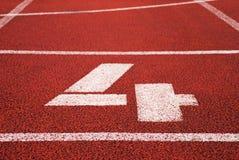 Nr. vier Weiße Bahnzahl auf roter Gummirennbahn, Beschaffenheit von Rennbahnen im Stadion Stockfoto