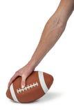 Närbild av den amerikanska fotbollsspelaren som förlägger bollen Arkivfoto