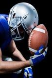 Närbild av den upprivna amerikanska fotbollsspelaren med bollen Arkivbilder