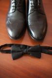 Närbild av gjort ljusare med mäns för naturligt ljus skor och fluga Royaltyfri Foto