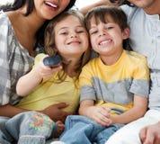 Närbild av gulliga barn som håller ögonen på TV:N med föräldrar Arkivbild