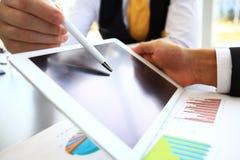Närbildbild av en kontorsarbetare som använder en touchpad för att analysera Arkivfoto