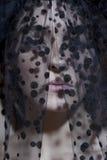 Närbilden av en ung kvinna i svart skyler att se bort Royaltyfria Bilder