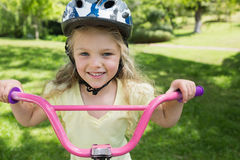 Närbilden av lilla flickan på en cykel på parkerar Royaltyfria Bilder