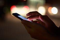 Närbildhand genom att använda telefonen i nattetid på gatan Royaltyfri Bild