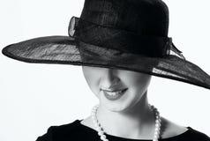 Närbildstående av en härlig kvinna i en svart hatt i retro s Fotografering för Bildbyråer