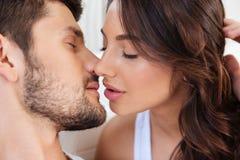 Närbildståenden av två vänner kopplar ihop att kyssa Arkivfoton