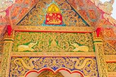 Ânsia dourada bonita no frontão da entrada da igreja em Wat Phra That Doi Tung, um de que é acreditado para conter o le fotografia de stock