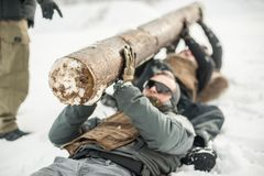 Nstructor and army soldiers have training with huge chump wood. Instructor and army soldiers in complete equipment have hard training with huge chump wood on stock images