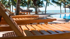 Nsun loungers near the hotel swimming pool. Tropical vacation in Asia, millennial concept. Sun loungers near the hotel swimming pool. Tropical vacation in Asia royalty free stock photo