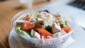 NTake去在塑料封装的沙拉用蕃茄和鸡 办公室工作者的一顿有用的快餐在工作场所 库存图片