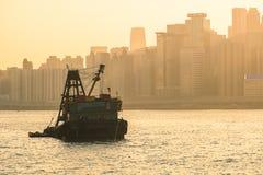Nternational-Behälter-Frachtschiff im Ozean mit Sonnenaufgang- und Dämmerungshimmel des Hong Kong-Stadtbildhintergrundes morgens, stockbild