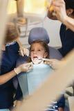 Ntists с пациентом во время зубоврачебной интервенции к девушке Стоковое Изображение RF