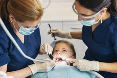Ntists с пациентом во время зубоврачебной интервенции к девушке Стоковые Фотографии RF