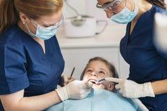 Ntists met een patiënt tijdens een tandinterventie aan meisje Stock Afbeelding